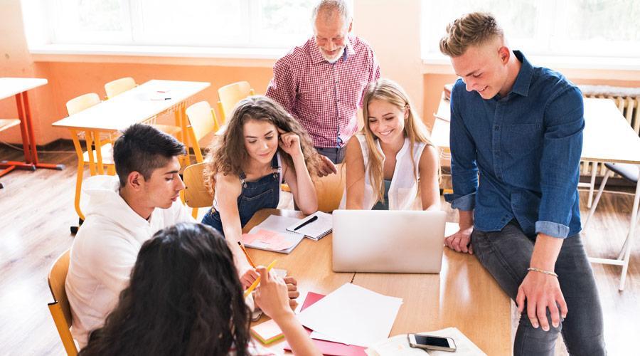 0e483289 Några elever sitter runt ett bord och diskuterar en skoluppgift tillsammans  med en lärare.