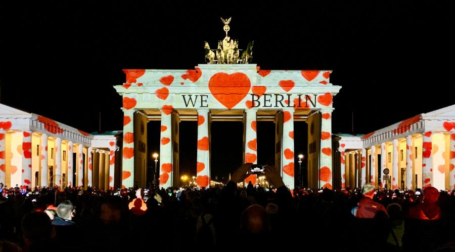 "Brandenburger Tor i Berlin under en ljusfestival när texten ""We <3 Berlin"" syns över hela byggnaden."
